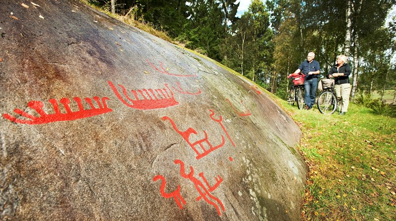 The rock art site Lövåsen and visitors with bikes.