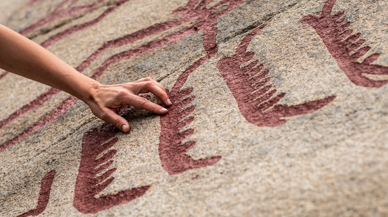 Hand touching a rock art boat.