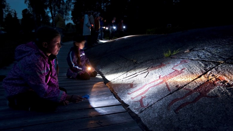Children looking at the Fossum carving using flashlights.